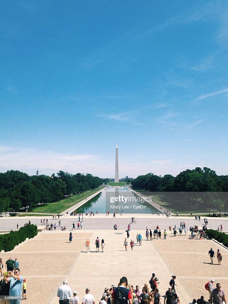 People Watching Washington Monument Against Blue Sky