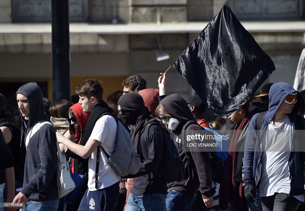People wave a black flag as they march during a protest against the government's planned labour law reforms in Nantes, western France, on May 3, 2016. High school pupils and workers protested against deeply unpopular labour reforms that have divided the Socialist government and raised hackles in a country accustomed to iron-clad job security. / AFP / LOIC
