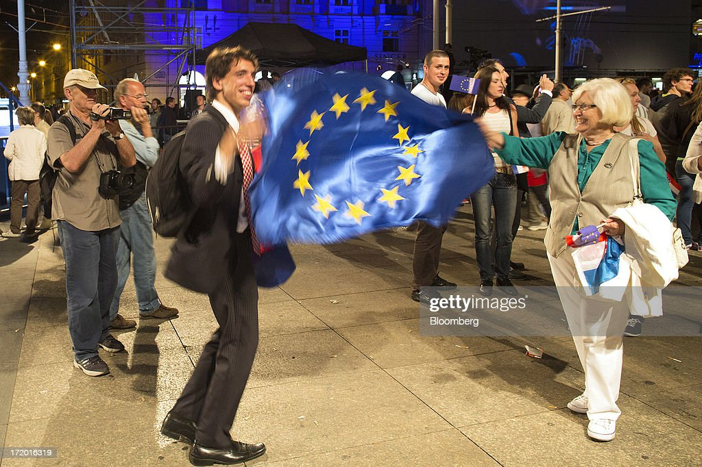 People wave a European Union (EU) flag during celebrations in Ban Jelacic square as Croatia marks it's entry into the European Union (EU) in Zagreb, Croatia, on Sunday, June 30, 2013. Croatia will become the European Union's 28th member at midnight, the bloc's first addition since Bulgaria and Romania joined in 2007. Photographer: Simon Dawson/Bloomberg via Getty Images