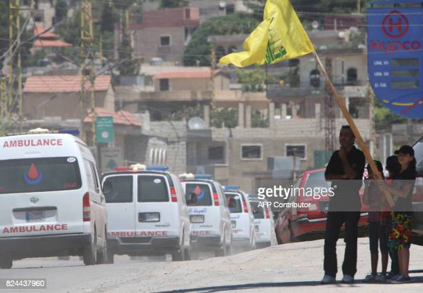 People wave a flag of the Lebanese Shiite Hezbollah movement as the group's ambulance convoy drives past carrying bodies of fighters killed in...