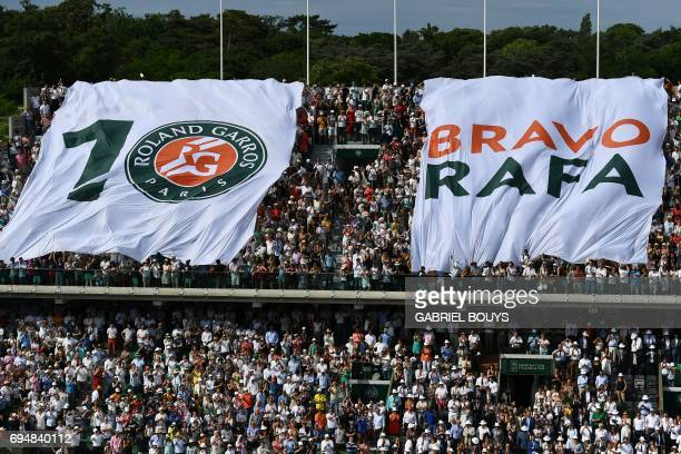 People wave a giant flag after Spain's Rafael Nadal won a record 10th French Open title against Stan Wawrinka in their final on June 11 June 2017 in...