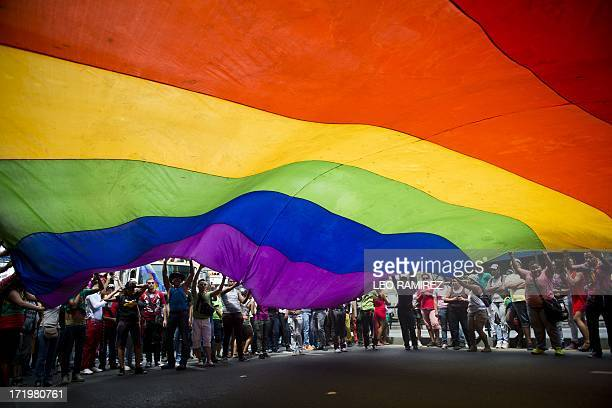 People wave a huge rainbow flag during the 35th Gay Pride Parade in downtown Caracas on June 30 2013 AFP PHOTO / Leo RAMIREZ