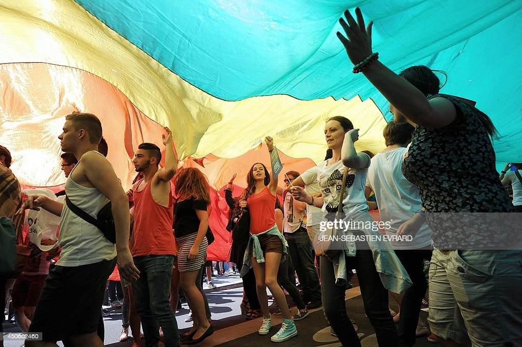 People wave a rainbow flag while taking part in the 13th annual local edition of the Gay Pride homosexual, bisexual and transgender visibility march on June 14, 2014, in Nantes, western France. Drag queens, civil rights activists and scantily clad gay and straight couples made their way through the city to the thumping of dance music.