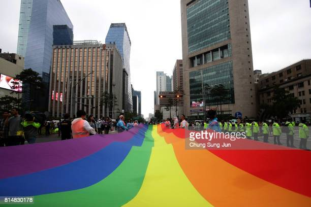 People wave a rainbow pride flag during the Korea Queer Culture Festival 2017 in front of City hall on July 15 2017 in Seoul South Korea The annual...