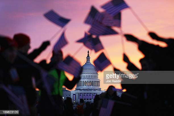 People wave American flags as people gather near the US Capitol building on the National Mall for the Inauguration ceremony on January 21 2013 in...