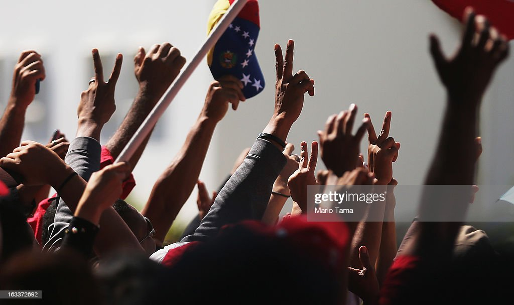 People wave and applaud as dignitaries arrive for the funeral for Venezuelan President Hugo Chavez outside the Military Academy on March 8, 2013 in Caracas, Venezuela. Countless Venezuelans have paid their last respects to Chavez and more than 30 heads of state were expected to attend the funeral today.