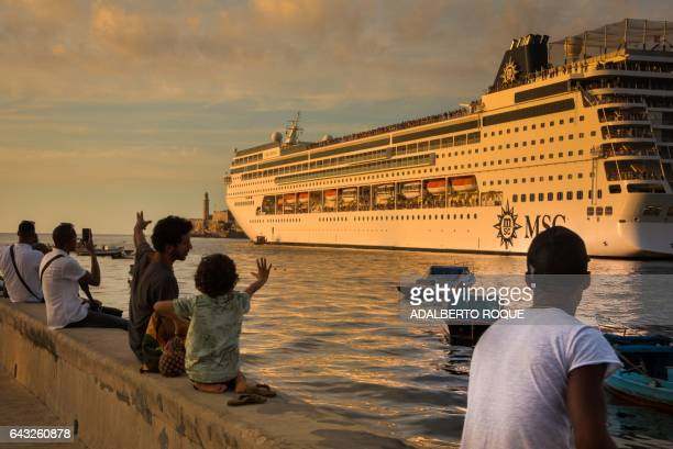 TOPSHOT People wave as a cruise ship leaves Havana's harbor on February 20 2017 / AFP / ADALBERTO ROQUE
