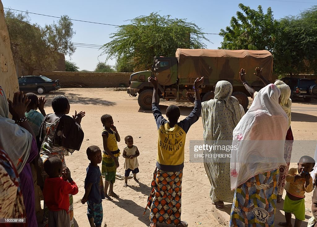 People wave as a French military convoy crosses on January 29, 2013 Timbuktu after French-led troops freed the northern desert city on January 28 from Islamist control. Hundreds of Malians looted Arab-owned shops on January 29 in Timbuktu as global donors pledged over 455 million US dollars (340 million euro) at a donor conference in the Ethiopian capital Addis Ababa for military operations in Mali and humanitarian aid to rout the radicals from the north. Sign reads 'The city of Timbuktu is founded on Islam and will be judged only by the Islamic law (sharia)).