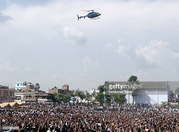 People wave as helicopter carrying Bollywood actor Ajay Devgn arrives at an election rally for the ongoing Bihar Assembly Elections on October 13...
