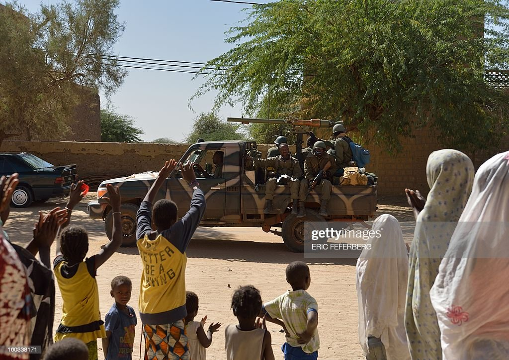 People wave as Malian soldiers on a pick-up truck cross on January 29, 2013 Timbuktu after French-led troops freed the northern desert city on January 28 from Islamist control. Hundreds of Malians looted Arab-owned shops on January 29 in Timbuktu as global donors pledged over 455 million US dollars (340 million euro) at a donor conference in the Ethiopian capital Addis Ababa for military operations in Mali and humanitarian aid to rout the radicals from the north. Sign reads 'The city of Timbuktu is founded on Islam and will be judged only by the Islamic law (sharia)). AFP PHOTO / ERIC FEFERBERG CAPTION ADDITION