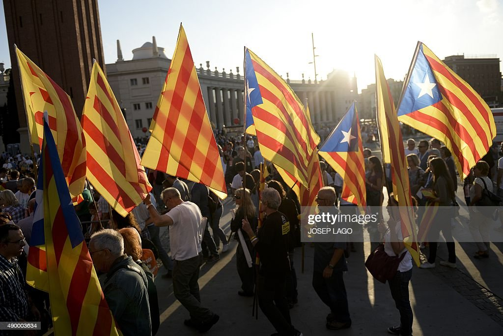 People wave Catalan and Catalan independence flags during the Catalan independence coalition 'Junts pel Si' party's final campaign meeting for the...