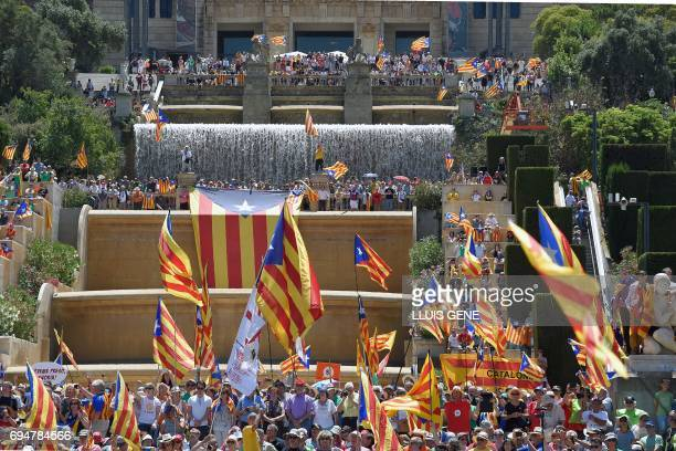 People wave Catalan proindependence 'estelada' flags and hold up placards during a demonstration dubbed 'Referendum is Democracy' organized by ANC...