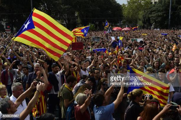 People wave Catalan proindependence 'Estelada' flags as they take part in a protest in Barcelona on October 2 2017 a day after hundreds were injured...