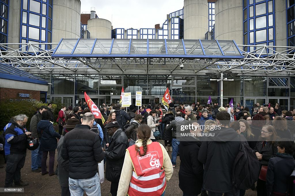 People wave CGT union flags as they gather in front of the Bobigny courthouse on April 29, 2016 to call for the release of two of their colleagues, arrested yesterday during demonstrations against the government's proposed labour law. At least 170,000 workers and students took to the streets across France on April 28, as clashes erupted in several cities with scenes of burning cars, stone-throwing protesters and police firing tear gas. / AFP / MARTIN