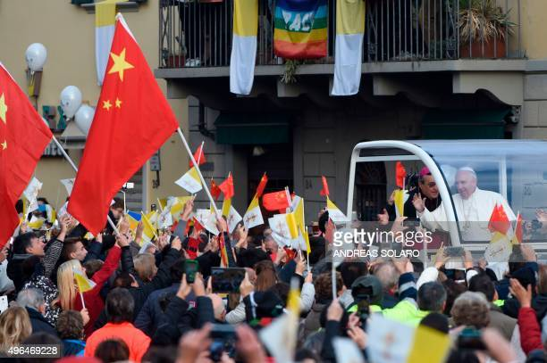 People wave Chinese national flags and Vatican flags as Pope Francis waves to the crowd from the popemobil in a street of Prato during his pastoral...