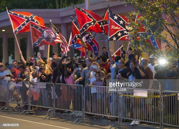 People wave Confederate Flags as US President Barack Obama arrives at his hotel in Oklahoma City Oklahoma July 15 2015 AFP PHOTO / SAUL LOEB