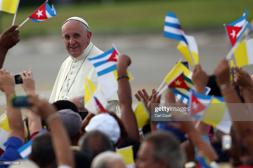 People wave Cuban and Papal flags as Pope Francis passes by as he arrives to perform Mass on September 20 2015 in Revolution Square in Havana Cuba...