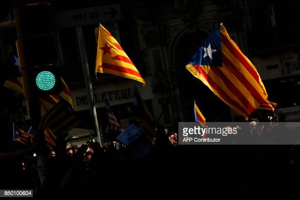 People wave 'Esteladas' during a protest in front of the Economy headquarters of Catalonia's regional government in Barcelona on September 20 2017...