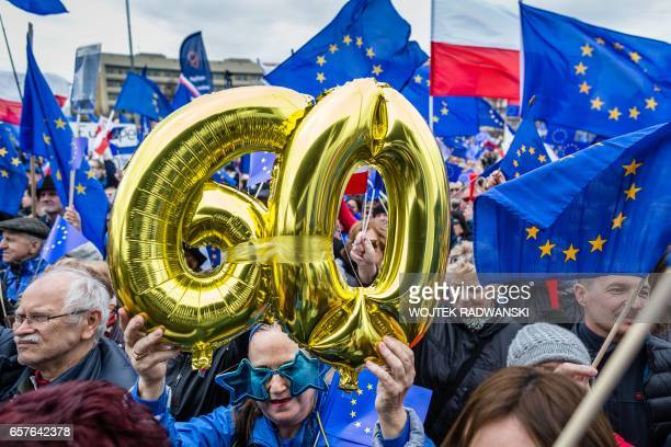 TOPSHOT People wave EU and Polish flags during a demonstration of the Committee for Democracy Defence in Warsaw on March 25 to mark the 60th...