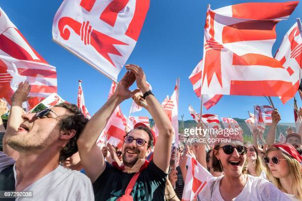 People wave flag of Jura canton as they celebrate after the commune of Moutier voted to join primarily Frenchspeaking canton Jura on the election day...
