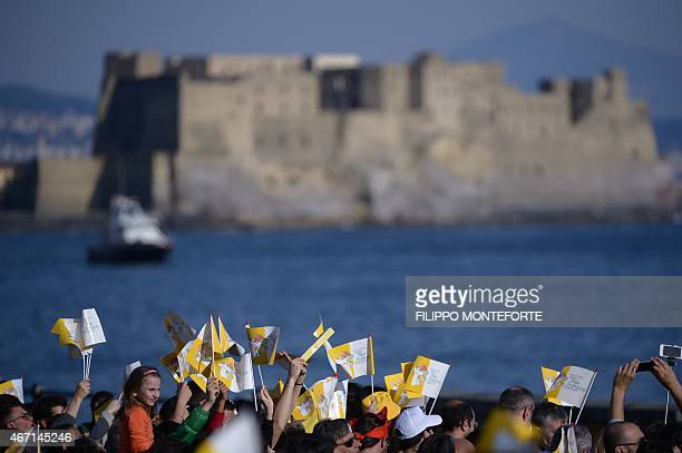 People wave flags along the sea with the Castel dell'Ovo in the background as they wait for the arrival of Pope Francis during a pastoral visit on...