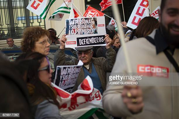 People wave flags and brandish placards during a protest against a reform of Spain's labour code in 2012 which maids say has led to lower salaries in...