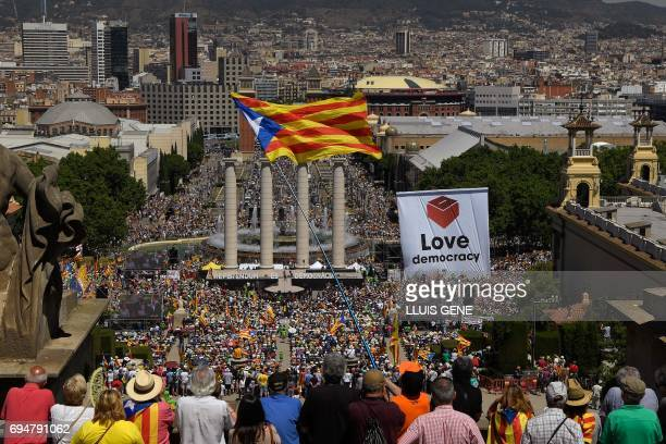 People wave flags and hold up placards during a demonstration dubbed 'Referendum is Democracy' organized by ANC AMI and Omnium Cultural in Barcelona...