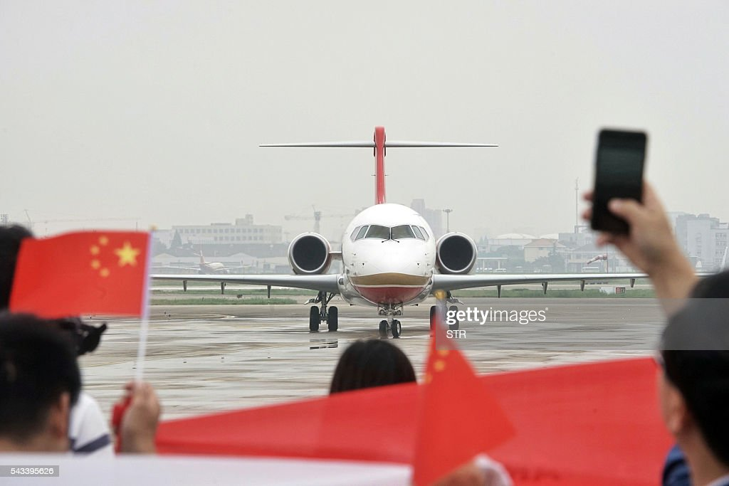People wave flags as China's first domestic regional jet ARJ21-700 arrives at Shanghai Hongqiao Airport after making its first flight from Chengdu to Shanghai on June 28, 2016. China's homegrown regional jet made its first commercial flight on June 28, Chengdu Airlines said, after months of delays raised questions about the country's ambitious plans for domestically produced planes. / AFP / STR / China OUT