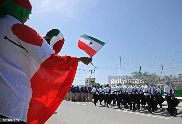 People wave flags as soldiers and other military personnel of Somalia's breakaway territory of Somaliland march past during an Independence day...