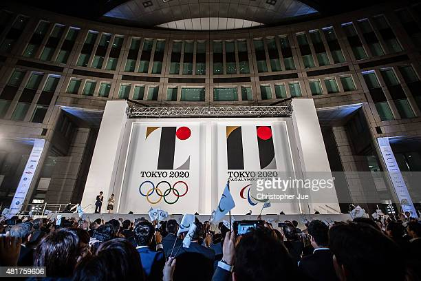 People wave flags as the new Olympic emblems are unveiled during a ceremony for the Tokyo 2020 Olympic and Paralympic Games at the Tokyo Metropolitan...