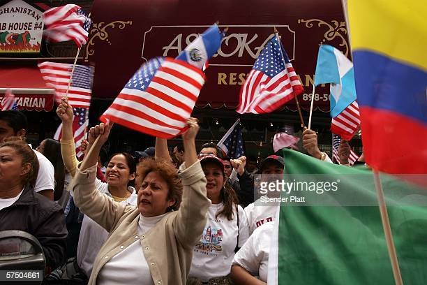 People wave flags as they participate in a proimmigrant demonstration May 1 2006 in the Queens borough of New York City Immigrants and their...