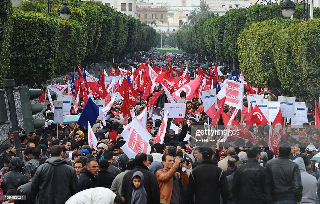 People wave flags during a gathering as part of the festivities marking the second anniversary of the uprising that ousted long-time dictator Zine El Abidine Ben Ali on January 14, 2013 in Tunis. Tunisians marked two years since the revolution amid a climate of uncertainty marked by social tension, a weak economy, threats from jihadists and a political impasse. AFP PHOTO / FETHI BELAID