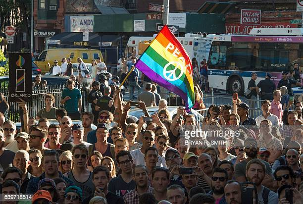People wave flags during a vigil in reaction to the mass shooting at a gay nightclub in Orlando Floridain New York on June 12 2016 Fifty people died...