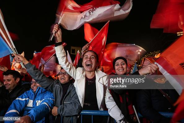 People wave flags outside the ruling AK Party headquarters after the party won a critical election after loosing a majority back in June on November...