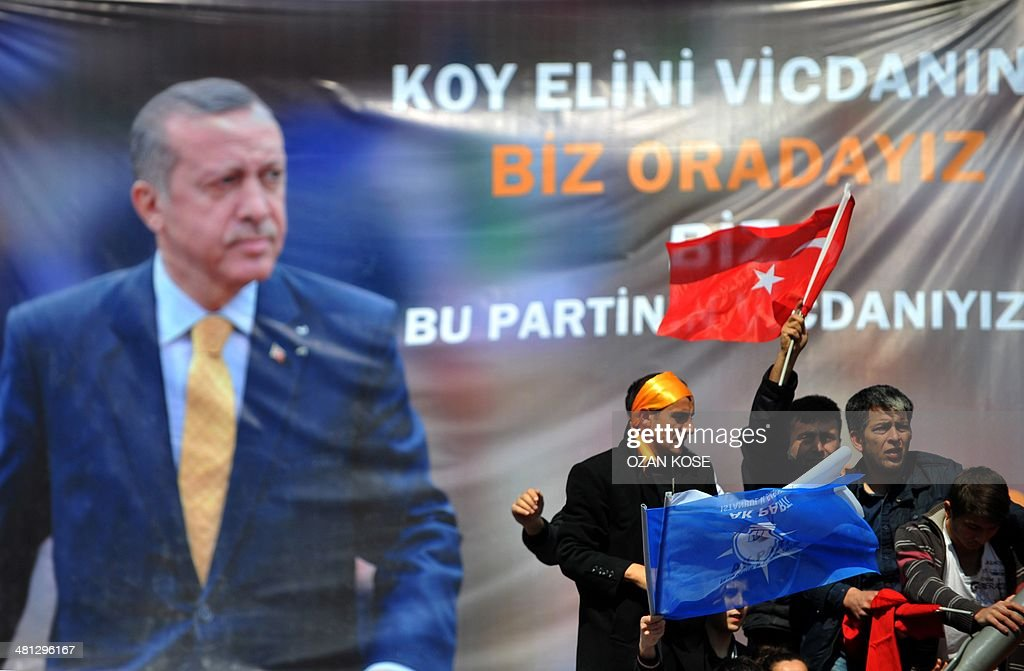 People wave flags with a poster showing Turkish Prime Minister Recep Tayyip Erdogan in the background during a rally of the Justice and Development Party (AKP) in the Maltepe district at the asia side of Istanbul on March 29, 2014. Turkey gears up for local elections on March 30 ahead of a presidential vote in six months and parliamentary polls next year. Erdogan and his Islamic-leaning party, after over a decade in power, face the first electoral test following months of political turmoil, with mass street protests and a corruption scandal spread via Twitter, Facebook and YouTube. Amid an atmosphere of distrust ahead of tomorow's election with over 50 million eligible voters, the CHP and tens of thousands of citizen volunteers plan to monitor the ballot count.
