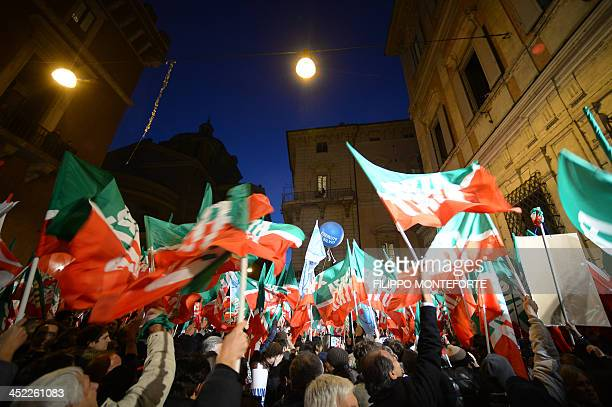 People wave 'Forza Italia' flags as they listen to the speech of Italy's former Prime Minister Silvio Berlusconi outside his private residence the...
