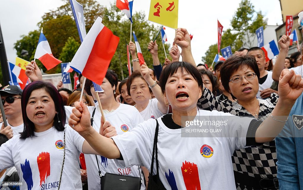 People wave French national flags as they march during a demonstration in Paris on August 21 organised by several associations of the Chinese...