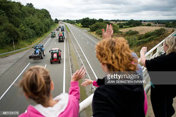 People wave from a bridge to farmers below them blocking the A81 highway with tractors as they protest against the low sales prices of their...
