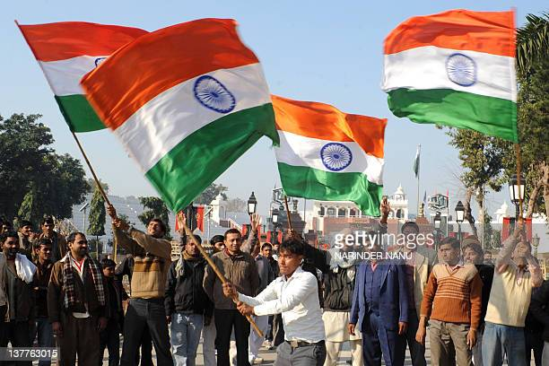 People wave Indian national flags during a ceremony to celebrate India's 63rd Republic Day at the IndiaPakistan Wagah border post on January 26 2012...