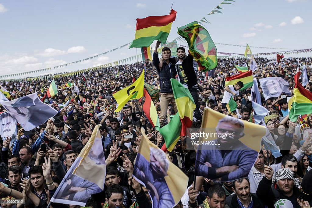 People wave Kurdish flags and flags bearing the portrait of jailed Kurdish leader Abdullah Ocalan as they celebrate Newroz, which marks the arrival of spring and the new year, in the Turkish town of Suruc, across the border from the Syrian town of Kobani, on March 17, 2015.