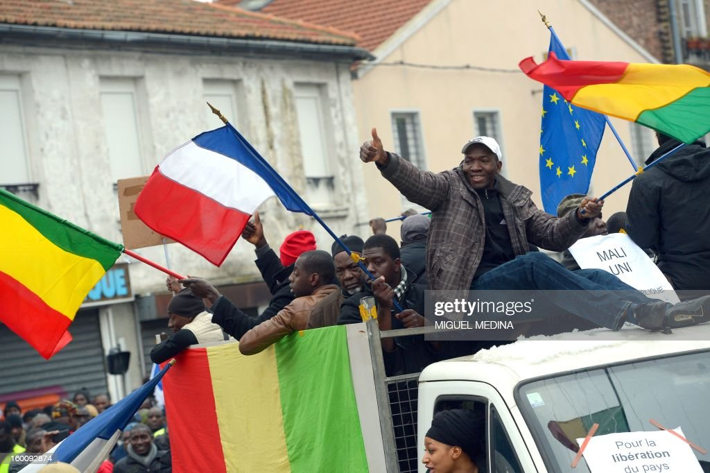 People wave Malian, French and European Union flags as they take part to a demonstration, organized by Malian associations, in support of the liberation forces of Mali on January 26, 2013 in Montreuil, near Paris.
