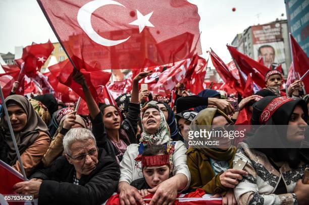 TOPSHOT People wave national flags and cheer during a rally in support of the Turkish President on March 26 2017 in Istanbul Turkish President Recep...