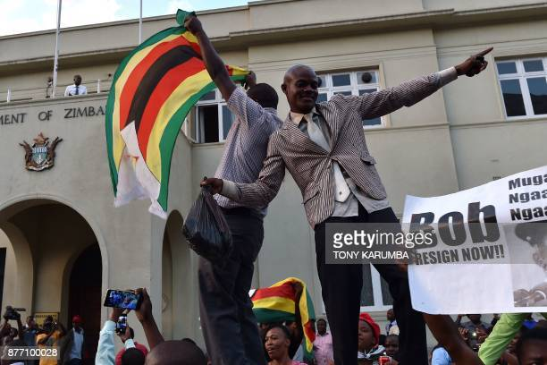 TOPSHOT People wave national flags as they celebrate outside the parliament in Harare after the resignation of Zimbabwe's president Robert Mugabe on...