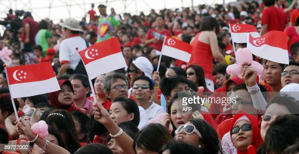 People wave national flags as they mark Singapore's 44th National Day on August 9 2009 In his National Day message Singapore Prime Minister Lee Hsien...