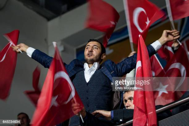 People wave national flags at a rally officially opening the AKP Party 'Yes' constitutional referendum campaign held at the Ankara Arena on February...