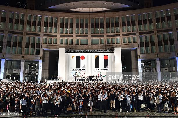 People wave Olympic flags as the logo marks of the Tokyo 2020 Olympic and Paralympic Games are unveiled at the Tokyo city hall on July 24 2015 The...