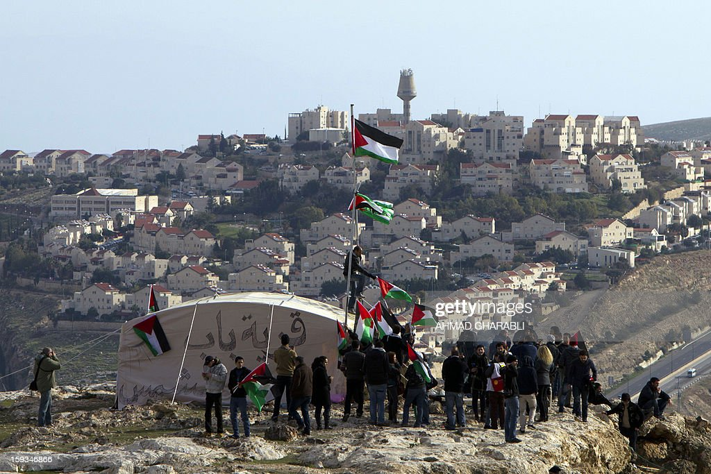 People wave Palestinian flags shouting slogans during a gathering of Palestinians alongwith Israeli and foreign activists at an 'outpost' named Bab al-Shams ('Gate of the Sun') set up between Jerusalem and the Jewish settlement of Maale Adumim in the Israeli-occupied West Bank, in an area where Israel has vowed to build new settler homes, on January 12, 2013. The Israeli occupation administration gave Palestinian activists an ultimatum to quit the protest camp in part of the West Bank, but hours after the deadline passed, there was no sign of any Israeli move to evict the protesters.