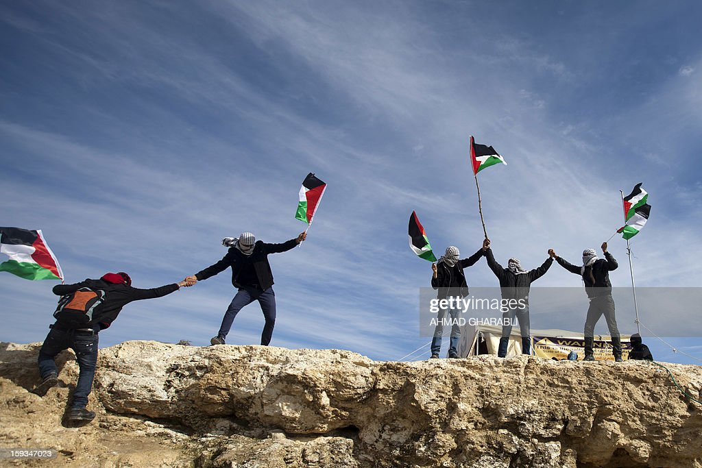 People wave Palestinian flags shouting slogans during a gathering of Palestinians alongwith Israeli and foreign activists at an 'outpost' named Bab al-Shams ('Gate of the Sun') set up between Jerusalem and the Jewish settlement of Maale Adumim in the Israeli-occupied West Bank, in an area where Israel has vowed to build new settler homes, on January 12, 2013. The Israeli occupation administration gave Palestinian activists an ultimatum to quit the protest camp in part of the West Bank, but hours after the deadline passed, there was no sign of any Israeli move to evict the protesters. AFP PHOTO/AHMAD GHARABLI