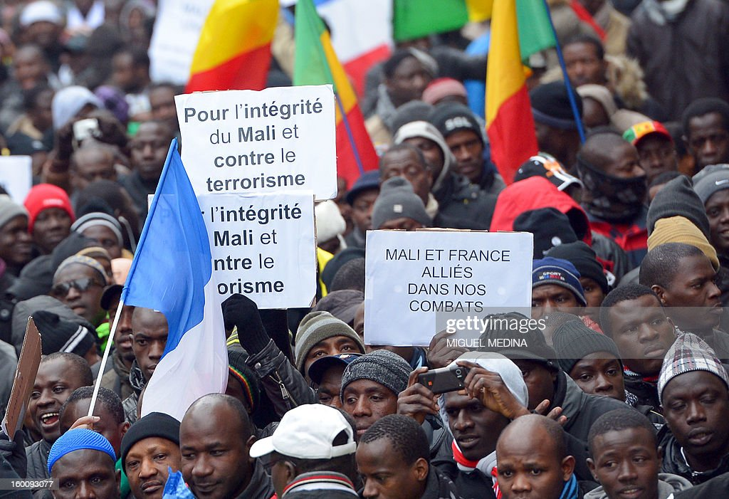 People wave placards during a demonstration, organized by Malian associations, in support of the liberation forces of Mali on January 26, 2013 in Montreuil, near Paris. Placards read 'For a united Mali, against terrorism' and 'Mali and France united in a same battle'.