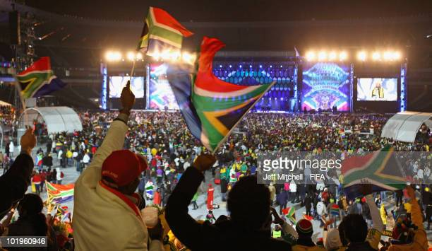 People wave South African flags at the FIFA World Cup Kickoff celebration concert at the Orlando Stadium on June 10 2010 in Soweto South Africa
